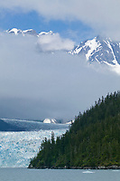 Chugach mountains visible through cloud layer over Meares glacier, Prince William Sound, Alaska