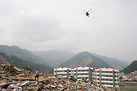 A helicopter flies over head as a resident searches for signs of trapped life on collapsed buildings in Beichuan, Sichuan, China. China now estimates the death toll to be around 50,000 as prospects of survival for those still buried diminishes..15 May 2008