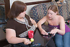 Woman with a disability chatting and looking at a text on a mobile phone with non disabled friend,