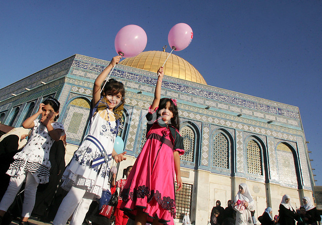 Palestinian girls hold a balloons in courtyards of  the Dome of Rock Mosque during the first day of Eid al-Fitr which marks the end of the Muslim fasting month of Ramadan, in the Al Aqsa Mosque Compound in Jerusalem's Old City, Friday, Sept. 10, 2010. Eid, one of the most important holidays in the Muslim world . Photo by Mahfouz Abu Turk