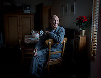 My Grandad Billy Henry looks outside as he waits for his breakfast in my fathers home in Staffordshire, December 20th 2013. After suffering from Altzhiemers for the past decade he now needs constant care, his wife of fifty-two years rests in bed after receiving a diagnosis that she has several tumours in her brain which had spread from two previous battles with cancer, leaving her with weeks to live. The couple moved from their flat in London to be cared for by family over what would be their last Christmas together. Having travelled the world on cargo ships in his twenties and teaching himself to play classical piano he takes comfort in simple activities such as sitting outside, listening to classical music and watching nature programs.