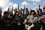 An opposition rebel played his guitar during a lull in fighting near the city of Ajdabiya, Libya, March 22, 2011. The previous week, loyalist forces of Col. Muammar Qaddafi attacked Ajdabiya, pushing rebels out and sending civilian refugees north to the opposition stronghold of Benghazi. France, Great Britain and the United States began a military campaign to impose a no-flight zone over Libya, which prevents Qaddafi forces from using air strikes against the rebels.