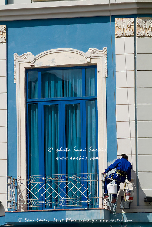 Worker painting a building facade on Prado Avenue, Havana, Cuba.