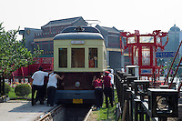 Chinese workers push a tram on Qianmen Street in Beijing on May 28, 2012. Qianmen Street has a history of more than 570 years. The shopping area was called Zhengyangmen Street during the Ming and Qing Dynasties, and finally named Qianmen Street in 1965. (Leica M9, 50mm f2)