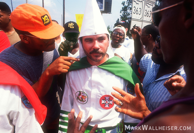 John BaumGardner, the Grand Dragon of the Florida Klavern of the Invisible Empire of the Knights of the Klu Klux Klan gets a face full of anti-Klan protesters at the intersection of Capitol Circle south and Woodville Highway where they came to hand out flyers during a membership drive.  Once word got out on the radio, the crowd swelled until the Leon County Sheriff's Dept arrived to protect the Klansmen.  Herbert Allan Boren the Grand Titan of the Florida Klavern of the Invisible Knights of the Klu Klux Klan was arrested on weapons charges much to the delight of the protesters August 26, 1989.