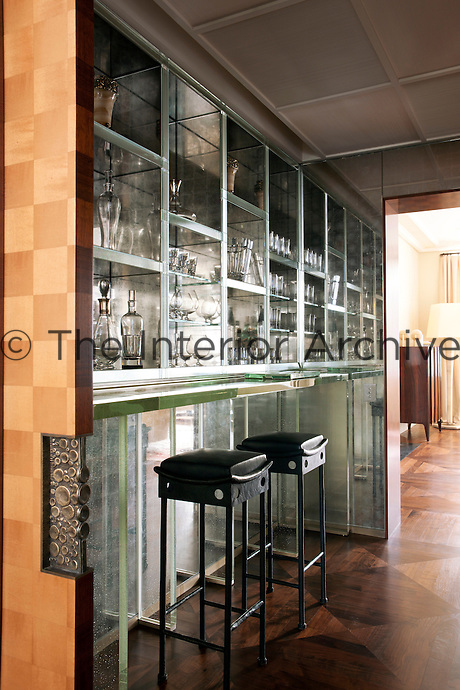 Concealed behind the sliding doors made of sycamore and decorated with bronze handles is a display cabinet and bar made of onyx and glass