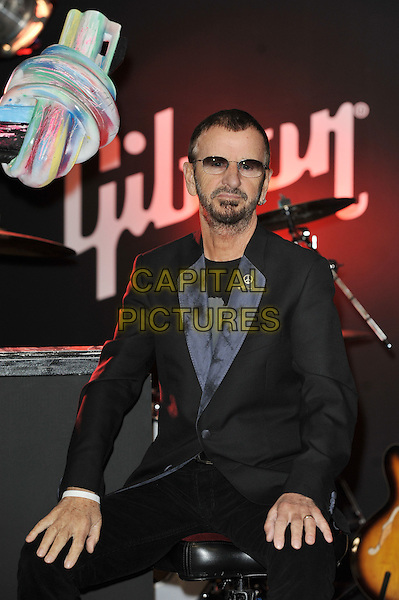 Ringo Starr.Unveiling of the 'Knotted Gun' statue for the Non Violence Foundation, Gibson Guitar Studio, London, England. .8th December 2011.half length black suit sunglasses shades beard facial hair sitting .CAP/MAR.© Martin Harris/Capital Pictures.