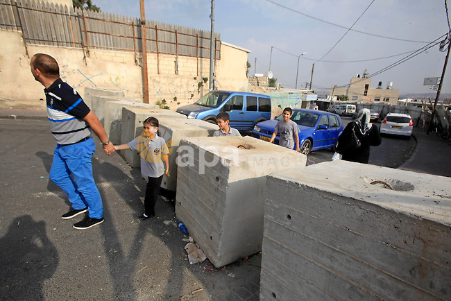 Palestinians walk between cement blocks at a newly erected checkpoint in Jerusalem's neighborhood of Jabal al-Mokaber on October 19, 2015. Israeli police began erecting a wall in east Jerusalem to protect a Jewish neighbourhood subject to firebomb and stone attacks launched from an adjacent Palestinian village. Photo by Mahfouz Abu Turk