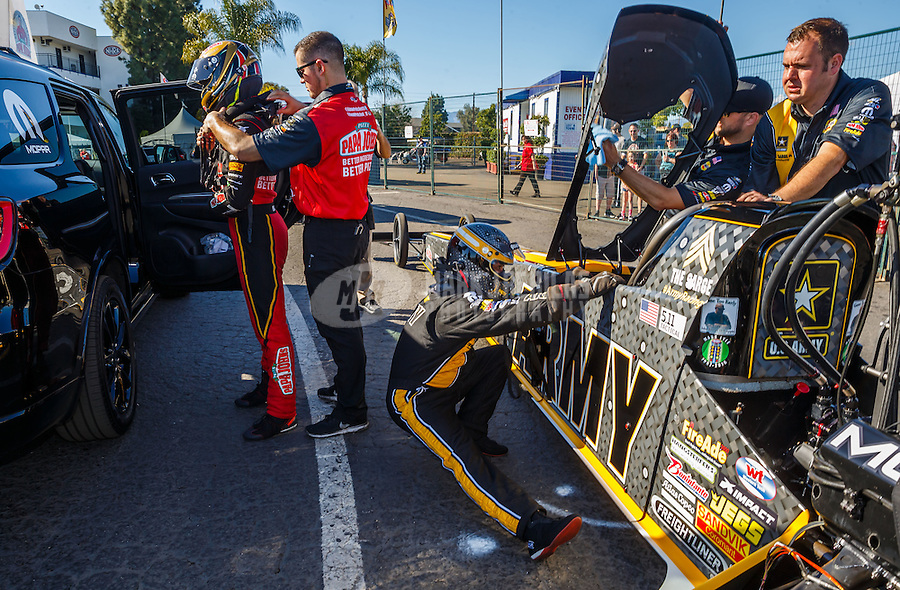 Feb 12, 2017; Pomona, CA, USA; NHRA top fuel driver Leah Pritchett (left) puts on her safety gear as Tony Schumacher stretches prior to getting into his car during the Winternationals at Auto Club Raceway at Pomona. Mandatory Credit: Mark J. Rebilas-USA TODAY Sports