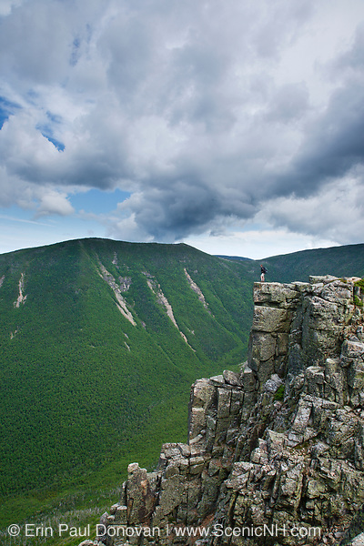 A hiker standing on the summit of Bondcliff in the Pemigewasset Wilderness of New Hampshire during the summer months. West Bond is on the other side of Hellgate Ravine. Bondcliff, Mount Bond, and West Bond were named in 1876 for Professor G.P. Bond of Harvard University.