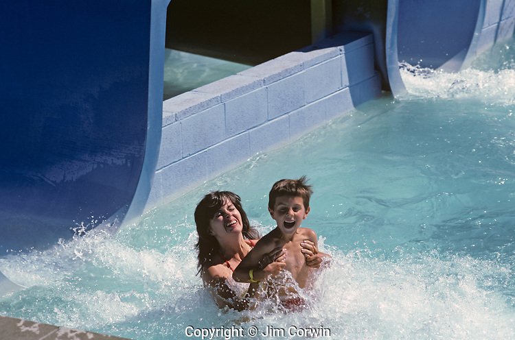 Mother and son enjoying a giant water slide splashing into water pool at end of ride .