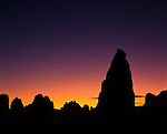 At sunset. More than 500 tufa spires (porous rock formed as a deposit from springs of streams), some as high as 140 feet (43 m), rise from the bed of the Searles Lake (dry) basin. Composed primarily of calcium carbonate (tufa), known as tufa pinnacles, formed underwater 10,000 to 100,000 years ago, now exist 2,000 feet above sea level in the Western Mojave Desert. Pinnacles are located within 3,800 acres (15 km2) of federal land managed by the Bureau of Land Management; are inside a BLM Area of Critical Environmental Concern (ACEC) designated to protect and preserve unique resources. Trona Pinnalces National Natural Landmark (Est. 1968), California Desert National Conservation Area.