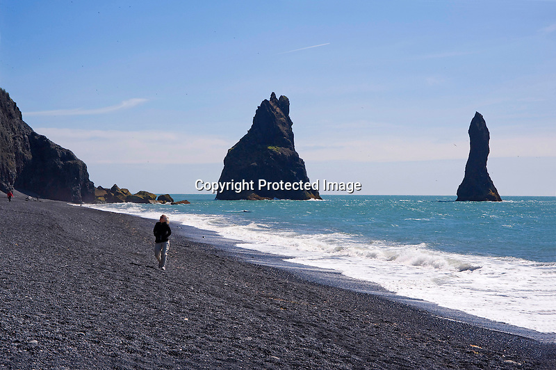 Enjoying Walk on Black Rocky Reynisfjara Beach at Vik on the South Coast of Iceland