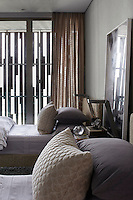 A guest bedroom decorated in a palette of greys and neutrals giving the room a cool, restful ambiance. The  American Redwood external cladding, functions as both a sunscreen and a decorative element, shading the room from the bright sunlight.