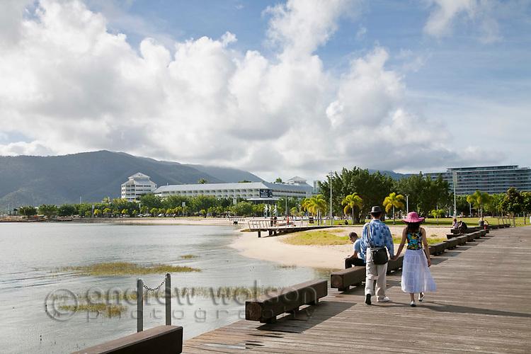 Couple walking along the Esplanade boardwalk.  Cairns, Queensland, Australia