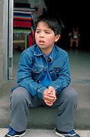 7 year old sitting on steps at Cinco de Mayo Festival .  St Paul  Minnesota USA