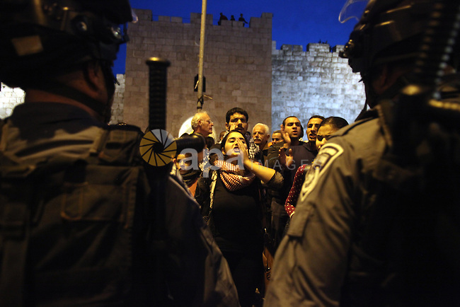 Palestinian Protestors confront Israeli border policemen during a demonstration showing solidarity with Bedouin Arabs who are against an Israeli government displacement plan for Bedouins in the southern Negev desert, in front of the Damascus Gate in the Old City of Jerusalem, on Nov. 30, 2013. Thousands of Israelis took to the streets across the country on Saturday to protest against the government plan to displace some 40,000 Arab Bedouins from their lands. Photo by Saeed Qaq