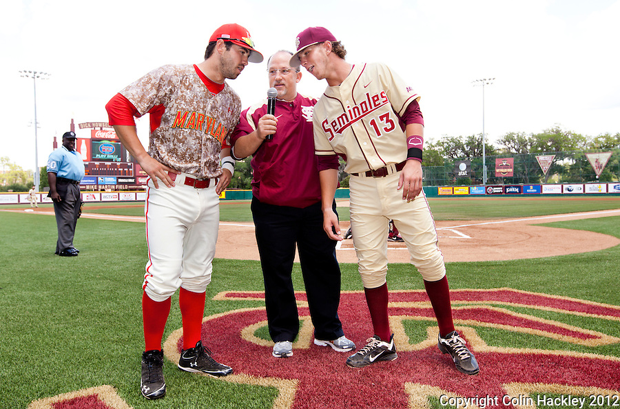 """TALLAHASSEE, FL 5/6/12-FSU-MARY050612 CH-Florida State's John Holland, right and brother Maryland's Ryan Holland are brought together by Chip Baker, director of baseball operations for the Seminoles to give the """"play ball"""" call before Sunday's game at the Dick Howser Stadium in Tallahassee. The Seminoles beat the Terrapins 10-3..COLIN HACKLEY PHOTO"""