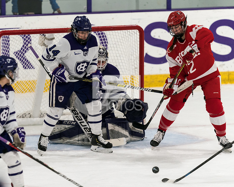 WORCESTER, MA - FEBRUARY 08: Allison Attea #14 of Holy Cross, Jada Brenon #31 of Holy Cross, and Kaleigh Donnelly #12 of Boston University focus on deflected puck during a game between Boston University and College of the Holy Cross at Hart Center Rink on February 08, 2020 in Worcester, Massachusetts.