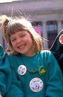 Girl age 6 smiling big at St Patricks day parade.  St Paul  Minnesota USA