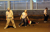 Pictured: Zombies awaiting players to walk past on a Cardiff street. Saturday 29 March 2014<br /> Re: Cardiff thrill-seekers were chased around the city last night by a horde of terrifying zombies as part of virtual apocalypse game 2.8 Hours Later.<br /> Starting in Grangetown, groups of zombie-enthusiasts walked, jogged, hid and run around a quarantined area of the city, which included Cardiff City Stadium and Ninian Park Primary School, to escape a deadly mass of infected undead.<br /> But it wasn't just zombies threatening to disturb the peace of the city – aggressive police and surveillance squads forcing people to stand up against walls and avoid their harmless friends for fear of spreading infection wreaked havoc in the quarantine.