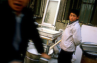 CHINA. Beijing. A young boy outside his family's restaurant in the Muslim district of 'Niu Jie'. 2005