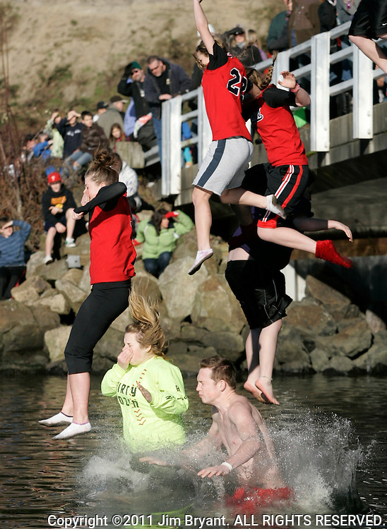 A group, jumping off the bridge,  is about to hit the icy waters during the  the 27th annual Polar Bear jump into the Burley Lagoon in Olalla, Washington on January 1, 2011. Over 300 hardy participants  braved the chilly lagoon waters to join in on the annual New Year's Day Tradition.  ©2011. Jim Bryant. All Rights Reserved.