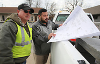 NWA Democrat-Gazette/DAVID GOTTSCHALK Terry Anderson (left), construction superintendent with the city of Springdale Public Works, and Jonathan Castillo, engineer with the city of Springdale Water Utilities, review plans Thursday, January 10, 2019, for an irrigation system on Emma Avenue in Springdale.