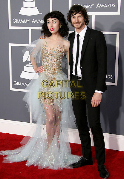 "Kimbra (Kimbra Lee Johnson) & Gotye (Wouter ""Wally"" De Backer).The 55th Annual GRAMMY Awards held at STAPLES Center, Los Angeles, California, USA..February 10th, 2013.grammys full length black suit white shirt tie beard facial hair blue tulle gold sheer sequins sequined dress hand on hip.CAP/ADM.©AdMedia/Capital Pictures."