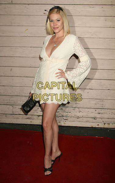 SHANNA MOAKLER.Maxim's Hot 100 Party 2008 at Paramount Studios, Hollywood, California, USA, .21 May 2008..full length cream long sleeved dress hand on hip low cut  lace bow .CAP/ADM/MJ.©Michael Jade/Admedia/Capital PIctures