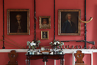 The gun racks flanking the portraits and bayonet holders above the doors were used by Sir Edward Leslie in the late 18th century