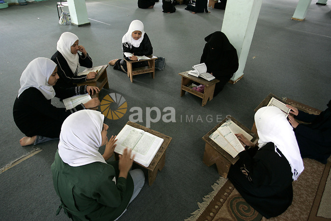 Palestinian girls read the Koran at a summer camp for the study of Islam's holy book organised by the Islamist movement Hamas in Rafah in the southern of Gaza Strip on June 19, 2011. Photo by Abed Rahim Khatib