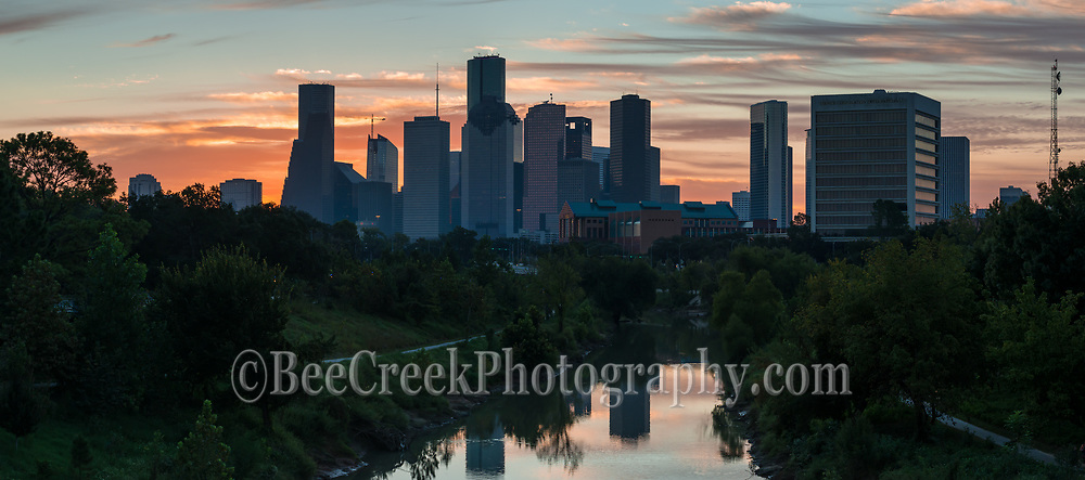 Houston skyline pano as sunrise was beginning to rise over the buffalo  bayou with the downtown high rise buildings in the background. This image was almost a silouette against this colorful sky right before the sunrise.   The water reflected the sky colors and Houston skyline into the water along the Buffalo Bayou in downtown part of the city. You can see the cities skyscrapers high rise building as they appear to line up along the banks of the bayou.  Houston has some of the tallest buildings in the southern US.  The JP Morgan Chase building is 1002 feet and the tallest in the southern US and then we have the Well Fargo high rise which comes in at 992 feet along with many other of the city skyscraper in view in this image. Houston has seven of the tallest ten buildings in Texas  Houston is also the most populous city with 2.3 million people in the area.  There are many area that make Houston the city it is today from the oil boom of the early 1900's to the energy industry of today, to sport with the Houston Astros, baseball, hockey, along with a first rate Medical Center, to NASA mission control and the Port of Houston all located in this city.