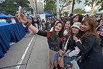 Filipina domestic workers in Hong Kong take a selfie during a beauty contest on Chater Road on a Sunday, their only day off. There are about 370,000 foreign domestic workers in Hong Kong–about 5 percent of the population–and just under half are from the Philippines. More than 98 percent of the workers are women, most of whom leave their families behind so that they can earn money to help their families survive.