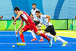 Simon Gougnard #22 of Belgium carries the ball while Agustin Mazzilli #26 of Argentina covers during Argentina vs Belgium  in the men's gold medal game at the Rio 2016 Olympics at the Olympic Hockey Centre in Rio de Janeiro, Brazil.