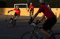 17 AUG 2014 - LONDON, GBR - A player from Mondial (in red and black) takes the ball up the court during the final against Triple Jay (in black) at the 2014 London Open Bike Polo tournament in Highbury Fields in London, Great Britain (PHOTO COPYRIGHT © 2014 NIGEL FARROW, ALL RIGHTS RESERVED)