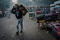 OLD DELHI, INDIA, JANUARY 11, 2016: A worker carries to put away blankets, rented to people overnight at a sleep market on January 11, 2016 in Old Delhi, India. <br /> Daniel Berehulak for The New York Times