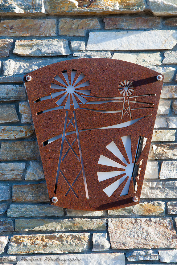 """A metal plate with windmill cutouts in front of tan rocks; this motif is frequently seen in the Grand Ave. corridor.  This was part of the 2015 rebuild of the Grand Avenue and Longview Drive intersection for Diamond Bar's 2015 """"Grand Avenue Beautification"""" project, landscape architecture for the project was by David Volz Design."""