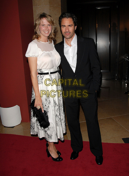 "ERIC McCORMACK & WIFE.The 15th Annual ""A Night at Sardi's"" Fundraiser and Awards held at The Beverly Hilton Hotel in Beverly Hills, California, USA..March 7th, 2007.full length black suit jacket white dress husband married bag purse.CAP/DVS.©Debbie VanStory/Capital Pictures"