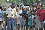 With encouragement from a Haitian police officer, women line up for food from the World Food Program during a massive distribution in Port-au-Prince, Haiti, less than three weeks after the January 12 earthquake that ravaged the Caribbean nation.
