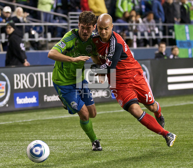 Toronto FC defender Mikael Yourassowsky battles Seattle Sounders FC forward Brad Evans for the ball during play at Qwest Field in Seattle Saturday April 30, 2011. The Sounders won the game 3-0.