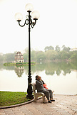 VIETNAM, Hanoi, a woman sits on a bench early in the morning, Hoan Kiem Lake and Pagoda
