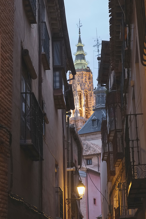 The approaching nightfall creates a mix of darkening lanes and brightening cathedral lights from this quiet backstreet in Toledo.