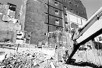 Mechanical digger at work on demolished buildings at a construction site.