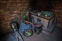 Uganda, Nyalaa. Sarah Mawejje, uses her BioLite stove in her kitchen at home. The stove charges light and her mobile phone.