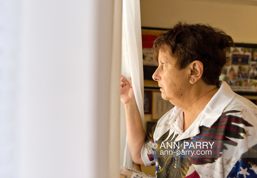 AUG. 11, 2012 - MERRICK, NEW YORK, U.S. - BARBARA BYRNE, a dual member of American Legion Merrick Post 1282 and its Auxiliary, looks out the window of post headquarters to watch guests from Long Island State Veterans Home at Stony Brook leave in bus at the end of a barbecue the post hosted for the vets. Byrne was a WAC (U.S. Women's Army Corps) in the 1960s.