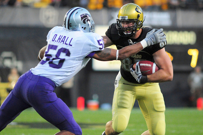 18 October 08: Colorado tight end Riar Greer (87) tries for yardage on a reception against Kansas State. Tackling Greer is K-state linebacker Olu Hall (56). The Colorado Buffaloes defeated the Kansas State Wildcats 14-13 at Folsom Field in Boulder, Colorado.