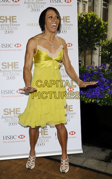 DAME KELLY HOLMES.The She Inspiring Women Awards 2009, Claridge's hotel, London, England..May 8th, 2009.full length yellow lace camisole silk satin dress white strappy sandals shoes hand mouth open funny .CAP/CAN.©Can Nguyen/Capital Pictures.