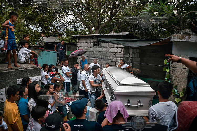Friends and family help carry the coffin of Raphael Cruz, 28, at his funeral in Manila North Cemetery.