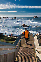 Tourist viewing ocean on stairs leading to beach at Bandon, Oregon.